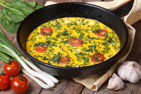Hot omelette with herbs, tomatoes in a pan, and vegetables on the table closeup  photo