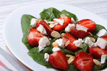 Fresh salad of strawberries, spinach, goat cheese and almond closeup. horizontal  photo