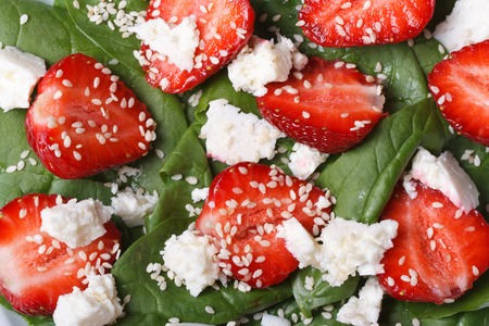 Background macro salad of strawberry , spinach, goat cheese and sesame. Horizontal  photo