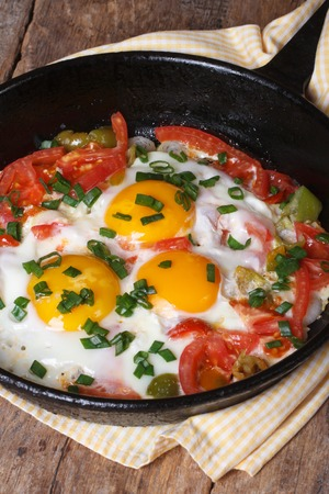 Fried eggs with tomatoes, peppers and onions in a pan on the table vertical closeup   photo