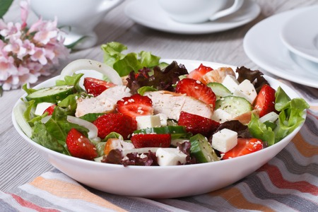 Salad with chicken, strawberries and vegetables close up on the table. horizontal  photo