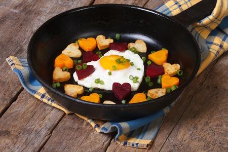huevos estrellados: Huevo frito en forma de coraz�n en la sart�n y corazones peque�os, zanahorias, remolachas y patatas Foto de archivo