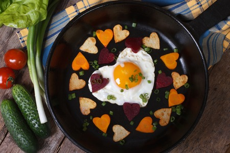 Egg and vegetables in the shape of heart. top view of the pan. Valentines Day  photo