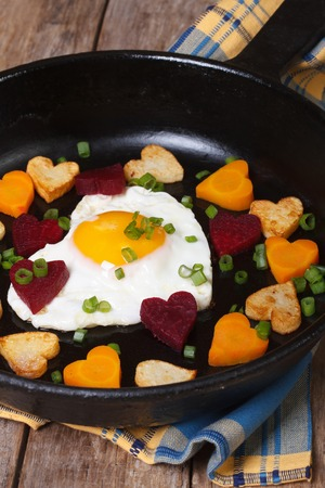 Egg in the form of heart in a pan with vegetables closeup. vertical  photo