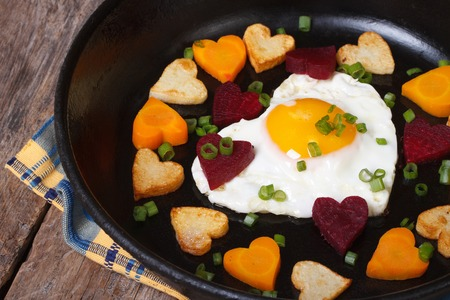 Romantic breakfast of fried eggs and vegetables in the shape of heart close up in a pan  photo