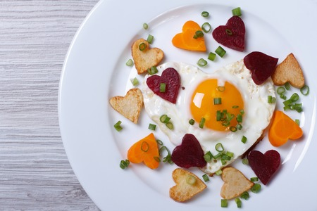 Romantic breakfast of fried hearts of vegetables and eggs on a plate. view from above.  photo