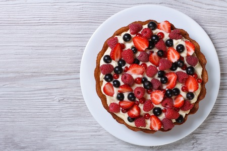 Delicious tart with fresh strawberries, raspberries and currants on the table. top view horizontal  photo