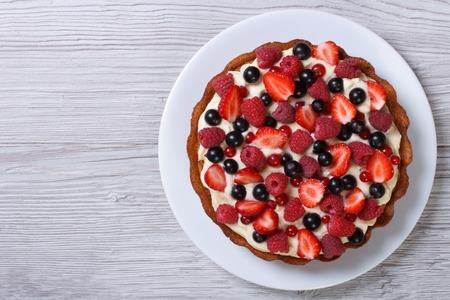 Leckere Torte mit frischen Erdbeeren, Himbeeren und Johannisbeeren auf dem Tisch. Ansicht von oben horizontal Lizenzfreie Bilder
