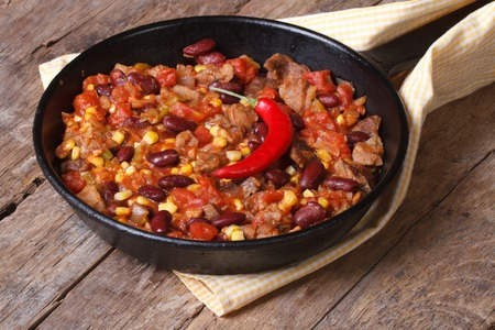 chili sauce: Mexican food is chili con carne in a frying pan on a wooden background closeup