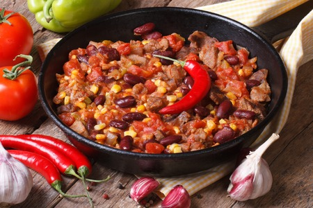 chili con carne close-up in a frying pan on a wooden background with the ingredients. horizontal