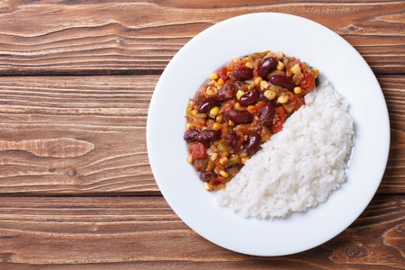Chili con carne and rice on a white plate on a wooden background. horizontal top view  photo