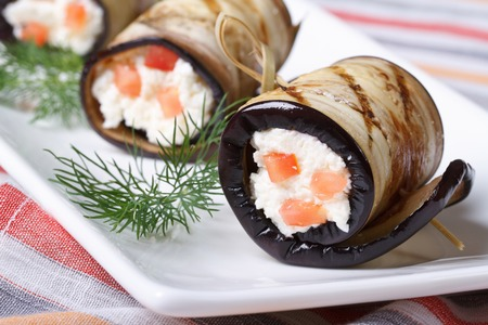 Eggplant rolls filled with cottage cheese and tomatoes on a plate closeup horizontal  photo