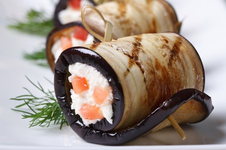 Eggplant rolls stuffed with cottage cheese and tomatoes on a plate macro horizontal  photo