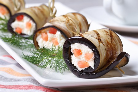 Eggplant rolls stuffed with cream cheese and tomatoes on a plate closeup horizontal  photo