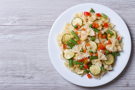 corn salad: Italian pasta farfalle with slices of vegetables on a wooden background. horizontal top view   Stock Photo