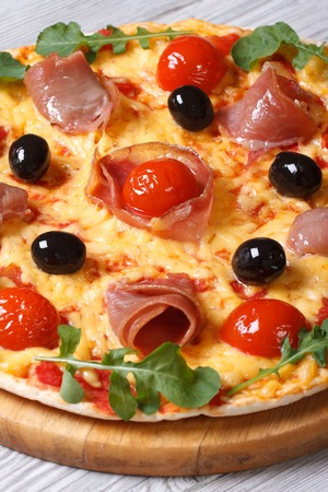 Italian pizza with prosciutto ham, tomatoes, black olives and arugula close-up on a wooden table. vertical   photo