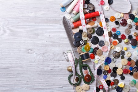 craft button: Background of old tools for sewing close up on wooden board top view horizontal  Stock Photo