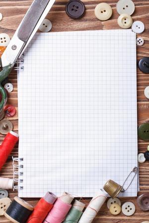 kit de costura: Antecedentes de la costura: tijeras, hilo, botones, cinta m�trica y el cuaderno de cerca la vista superior vertical,