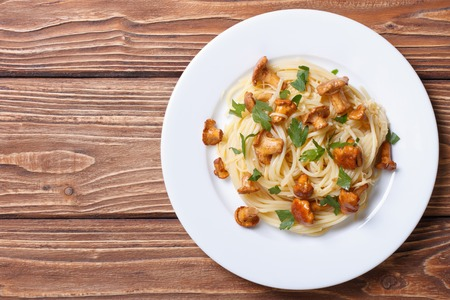 pasta: Espaguetis de pasta con rebozuelos setas en una vista desde arriba fondo de madera Foto de archivo