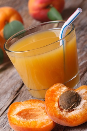 Apricot nectar with fruit halves closeup on a wooden table. vertical   photo
