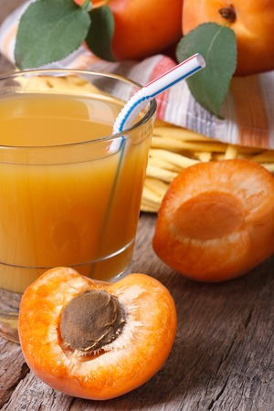 Apricot juice with fruit halves closeup on background basket with fresh fruit. vertical   photo
