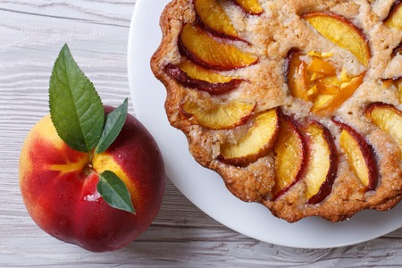 fruit tart and fresh peach closeup on a wooden table top view horizontal   photo