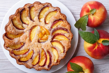 peach tart and fresh fruit closeup on wooden background horizontal view from above   photo