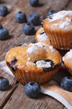 Delicious blueberry cupcakes closeup on a wooden table. vertical