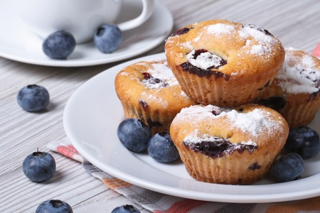 Blueberry muffins on a white plate and coffee closeup on a wooden table. horizontal   photo