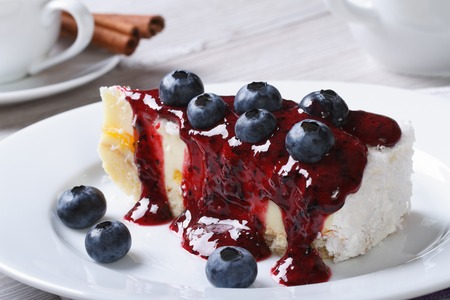 Cheesecake with blueberries on white plate closeup and coffee on the table horizontal   photo