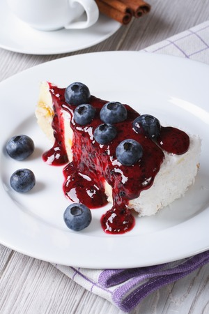 Blueberry cheesecake with berry sauce closeup on table top view vertical  photo