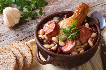 Bean soup with chicken legs and sausages in a bowl on the table horizontal  photo