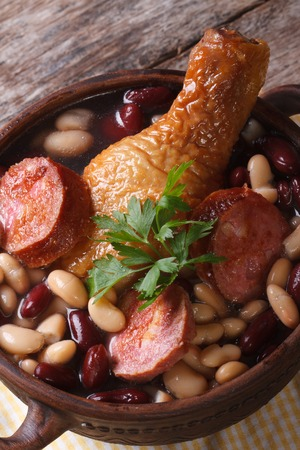 red and white beans with chicken legs and sausages in a bowl on the table. close up vertical  photo