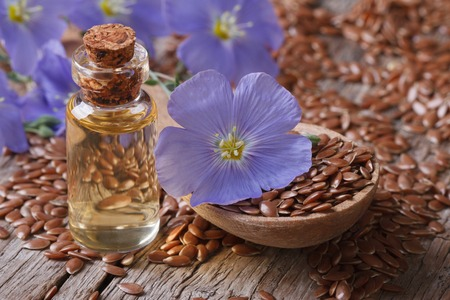 flax seeds in a spoon and oil in a bottle on the table  Stock Photo