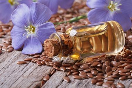 Vlaszaden, blauwe bloemen en olie in een fles op de tafel Stockfoto
