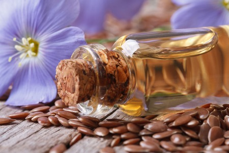 flax seed oil: flowers and flax seed, oil in glass bottle macro on wooden background