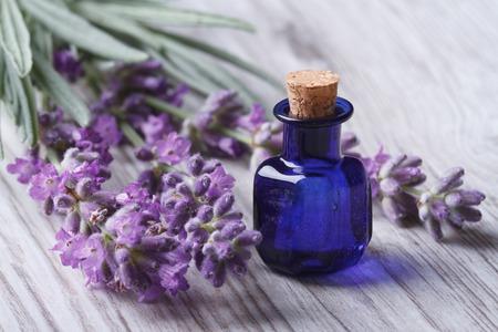Lavendelöl in einer Glasflasche auf einem Hintergrund von frischen Blumen.