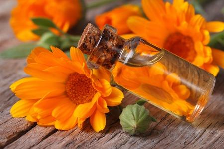 Ringelblumenöl in einer Glasflasche auf einem alten Tisch Nahaufnahme