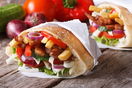 Doner kebab with meat and vegetables in pita bread wrapped in paper close-up on the table and ingredients horizontal  photo
