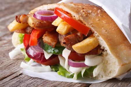 Doner kebab with meat, vegetables and fries in pita bread wrapped in paper close-up on the table horizontal  photo