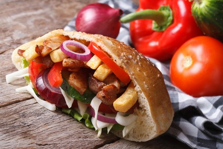 delicious shawarma with meat, vegetables and fries in pita bread closeup horizontal  photo