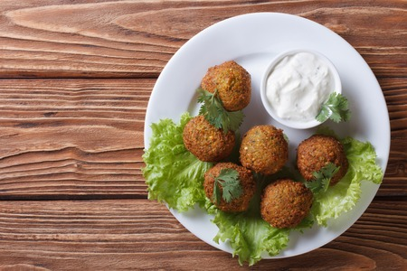 falafel: falafel on a white plate with sauce tzatziki close-up view from above horizontal