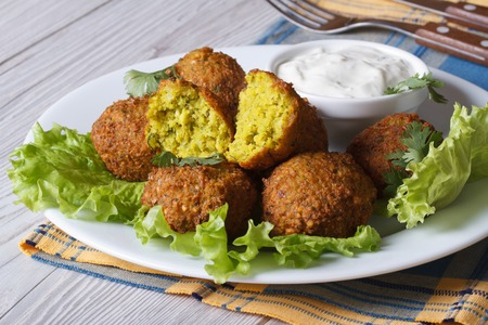 delicious falafel on lettuce with tzatziki sauce close-up on the table. horizontal