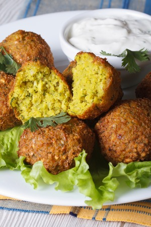 falafel with lettuce and tzatziki sauce closeup on a white plate on the table. vertical  photo