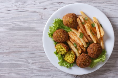 lebanese food: falafel with French fries, lettuce on a white plate top view horizontal