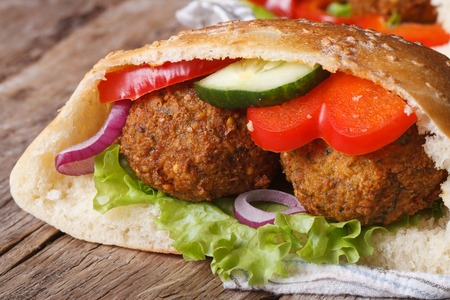 falafel: falafel with fresh vegetables in pita bread close-up on wooden table horizontal