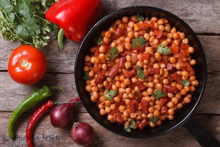 Chickpeas with chorizo ??in a pan close-up and with the ingredients on the table horizontal top view   Stock Photo