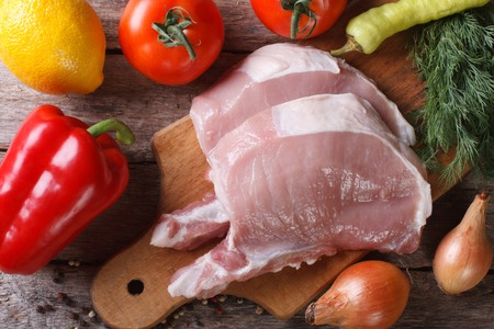 two pieces of raw pork meat on a cutting board close-up and fresh vegetables top view   photo