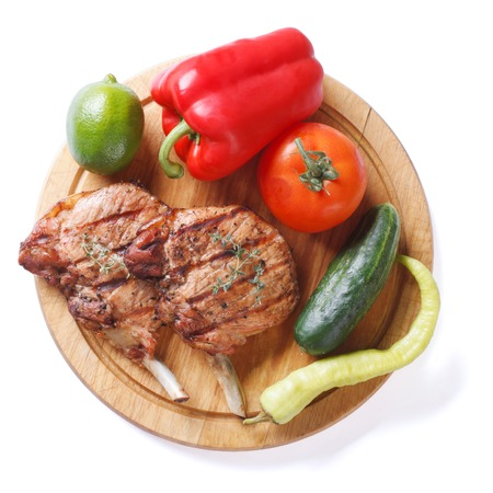 two pieces of of grilled pork and vegetables on a cutting board isolated on white background close-up view from above   photo