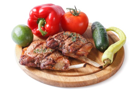 two pieces of of grilled pork and vegetables on a cutting board isolated on white background close up   photo